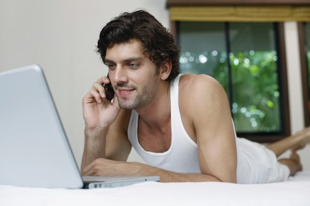 Man using laptop while talking on the phone Stock Photo - 6974177
