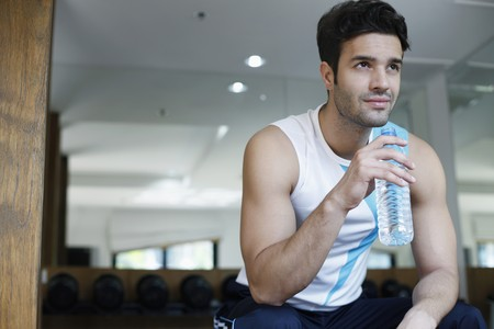 Man sitting down holding plastic water bottle Stock Photo - 6974193