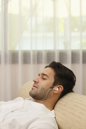 Man listening to music on portable mp3 player Stock Photo - 6974228