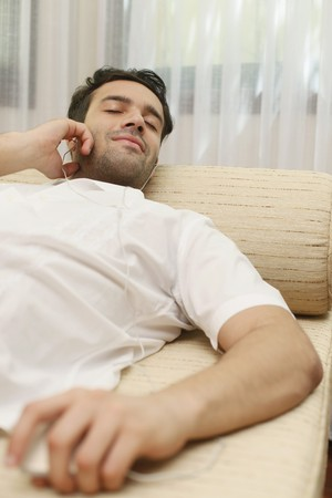 southeastern european descent: Man listening to music on portable mp3 player Stock Photo