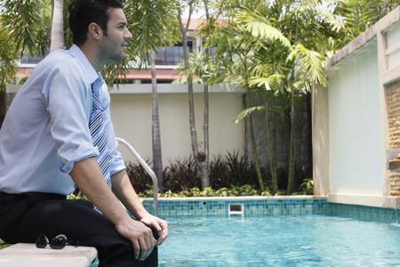 Businessman sitting with feet in swimming pool Stock Photo - 6974235