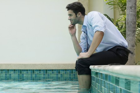 Businessman sitting with feet in swimming pool, contemplating Stock Photo - 6974238