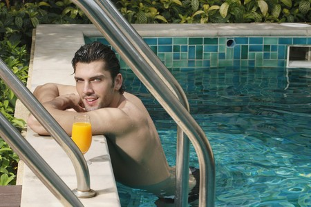 Man resting at the edge of the pool with a glass of orange juice at the side Stock Photo - 6974247