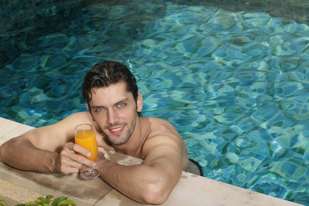 Man at the edge of the pool holding a glass of orange juice Stock Photo - 6974249
