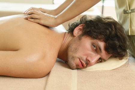 lastone therapy: Massage therapist giving man lastone therapy Stock Photo