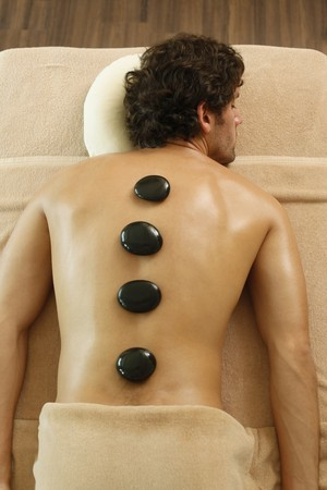 thai ethnicity: Hot stones on mans back Stock Photo