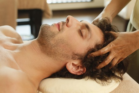 Massage therapist massaging mans head Stock Photo