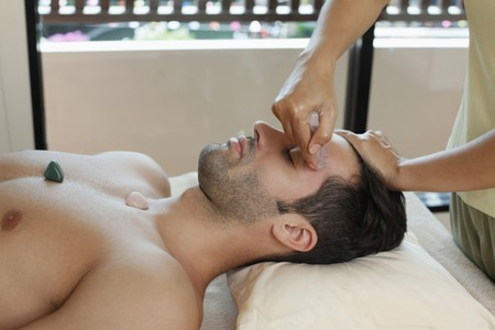 Man receiving crystal healing treatment