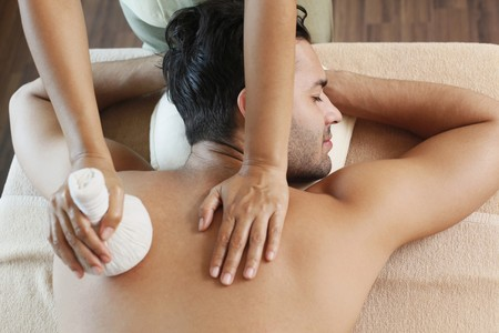 Man receiving a herbal pack massage from a massage therapist Stock Photo - 6974295