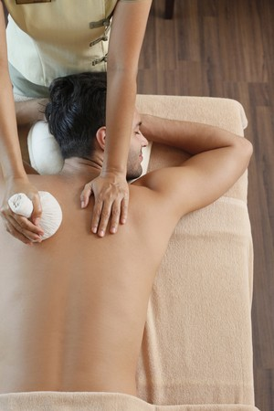 thai ethnicity: Man receiving a herbal pack massage from a massage therapist