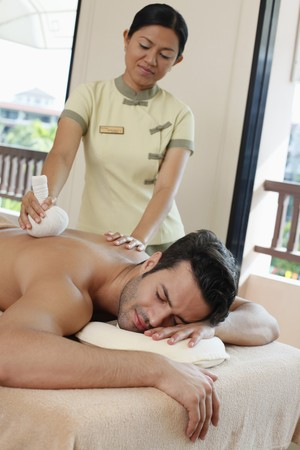 Man receiving a herbal pack massage from a massage therapist Stock Photo - 6974297