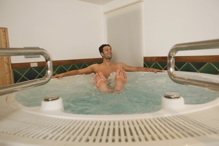 southeastern european descent: Man relaxing in hot tub with feet showing from water surface