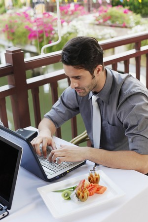 Businessman using laptop during lunch at restaurant Stock Photo - 6974318