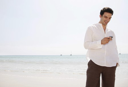 southeastern european descent: Man text messaging on the phone at the beach