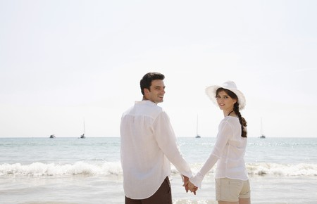Man and woman holding hands on beach photo