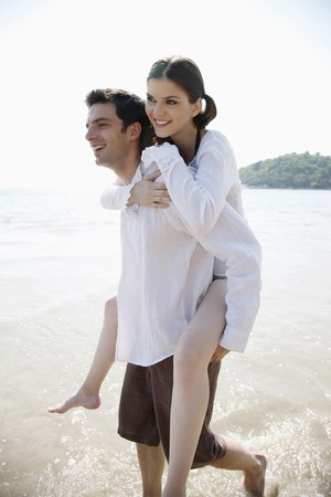 Man giving woman a piggy back ride on beach Stock Photo - 7086538