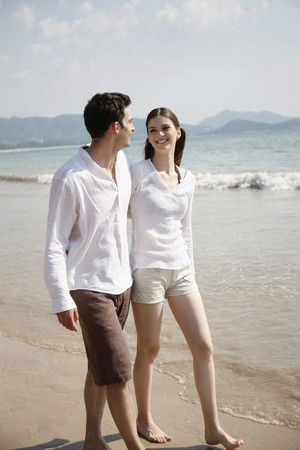 Man and woman walking along the beach Stock Photo - 7086542