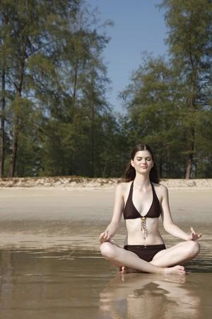 Woman meditating on beach Stock Photo - 7086545