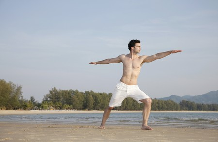 Man practising yoga on beach photo