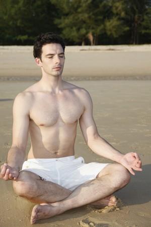 Man meditating on beach photo