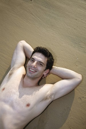 nackte brust: Mann mit nackten Brust mit den H�nden hinter dem Kopf am Strand liegend