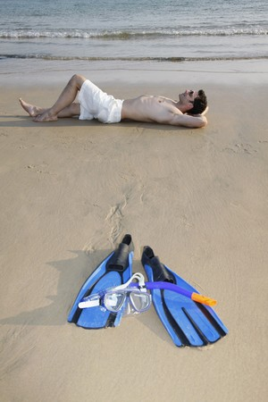 Man with bare chest lying down with hands behind head on beach photo