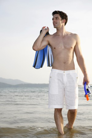 Man carrying snorkeling gear photo
