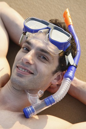 Man with scuba mask lying down with hands behind head on beach Stock Photo - 7077046