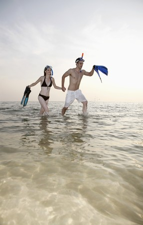 southeastern european descent: Man and woman running on beach with snorkeling gear Stock Photo