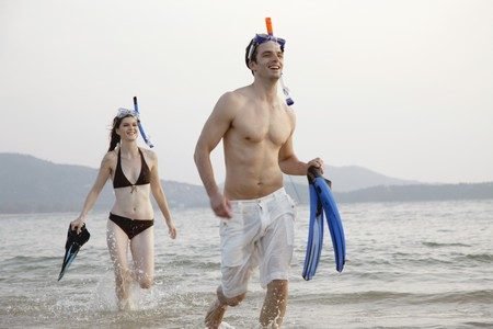 Man and woman running on beach with snorkeling gear Banque d'images - 7076980
