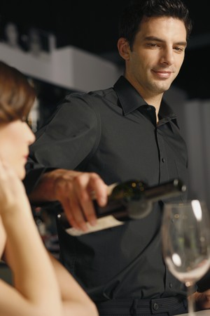 Man pouring wine into woman's glass Stock Photo - 7076987
