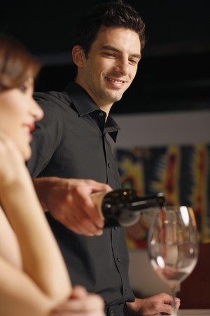 Man pouring wine into woman's glass Stock Photo - 7077000