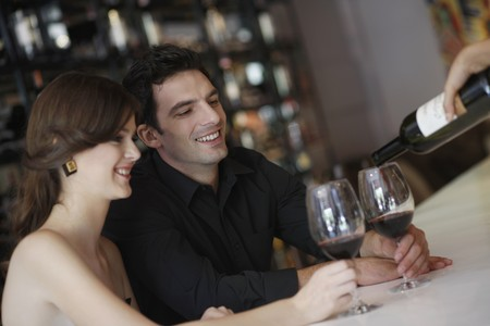 Man and woman having their glasses filled up Stock Photo - 7077021