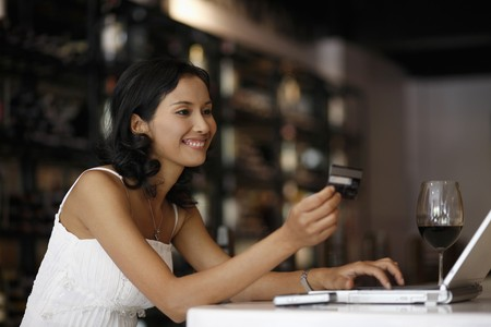 Woman looking at credit card while using laptop photo
