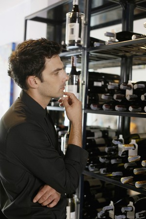 Man looking at wines in a restaurant photo