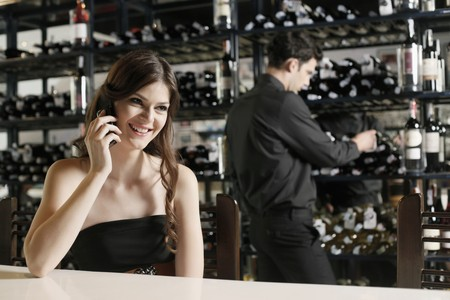 Woman talking on the phone, man selecting wine bottle in the background Stock Photo - 7077014