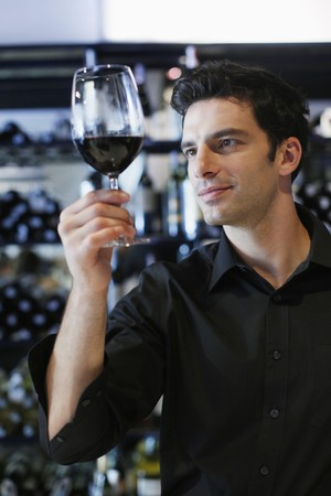 Man inspecting a glass of red wine