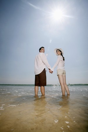 Man and woman holding hands while standing at the beach photo