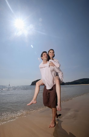 Man giving woman a piggy back ride on beach photo