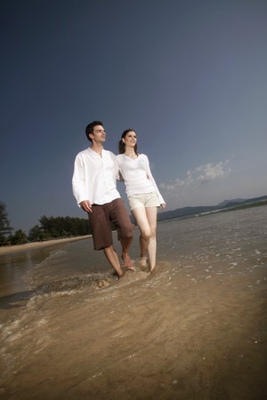 Man and woman walking along the beach photo