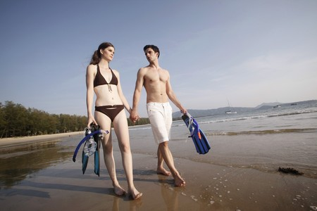 Man and woman carrying snorkeling gear photo