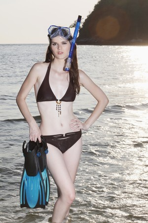 Woman with snorkeling gear posing on the beach photo