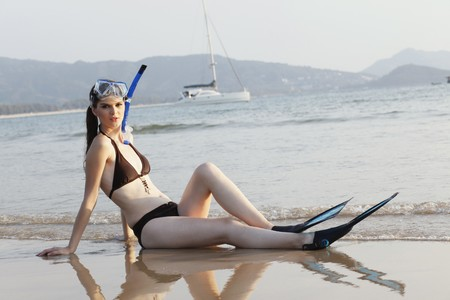 Woman with snorkeling gear sitting on the beach photo