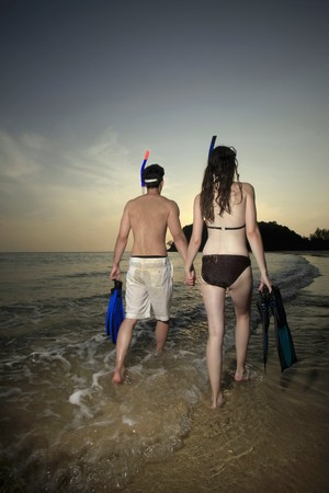 Man and woman carrying snorkeling gear Stock Photo - 7077022