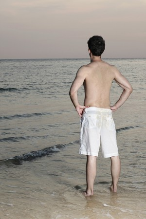Man standing with arms akimbo on the beach Stock Photo - 7077049
