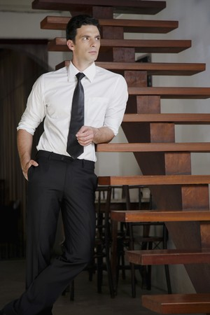 southeastern european descent: Businessman leaning against the stairs and looking away