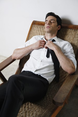 southeastern european descent: Businessman loosening his necktie while resting on lounge chair Stock Photo