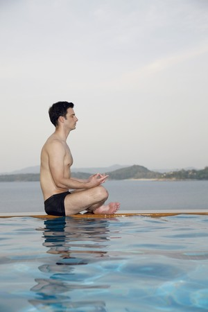 southeastern european descent: Man meditating by edge of swimming pool