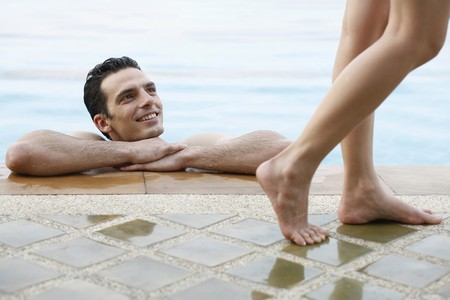 southeastern european descent: Man in pool looking at woman walking by Stock Photo