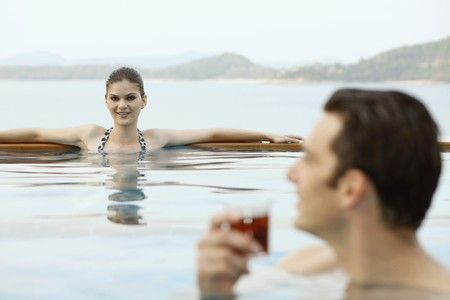 Woman relaxing in pool, man with a glass of tea photo